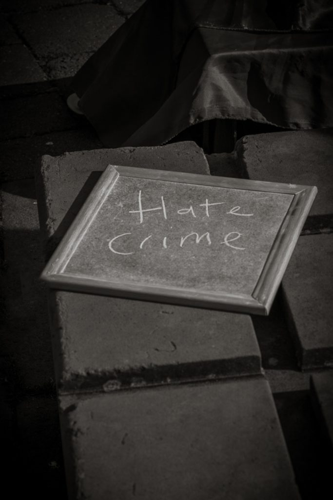 A simple black & white image of a small chalkboard upon which are written two words, Hate Crime. It belonged to one of the performers at the Worcester Pride festival 2017.
