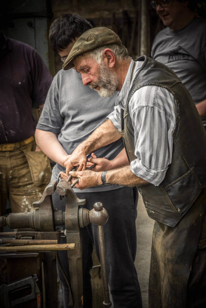 A 3/4 length colour image of an old & bold blacksmith, who is seen working at a vice in a smithy. He is bearded and he wears a traditional leather jerkin over a striped 'Granddad' style shirt, and has a leather apron around his waist. He has a flat cap upon his head. There is a teenager watching him intently over his right shoulder.