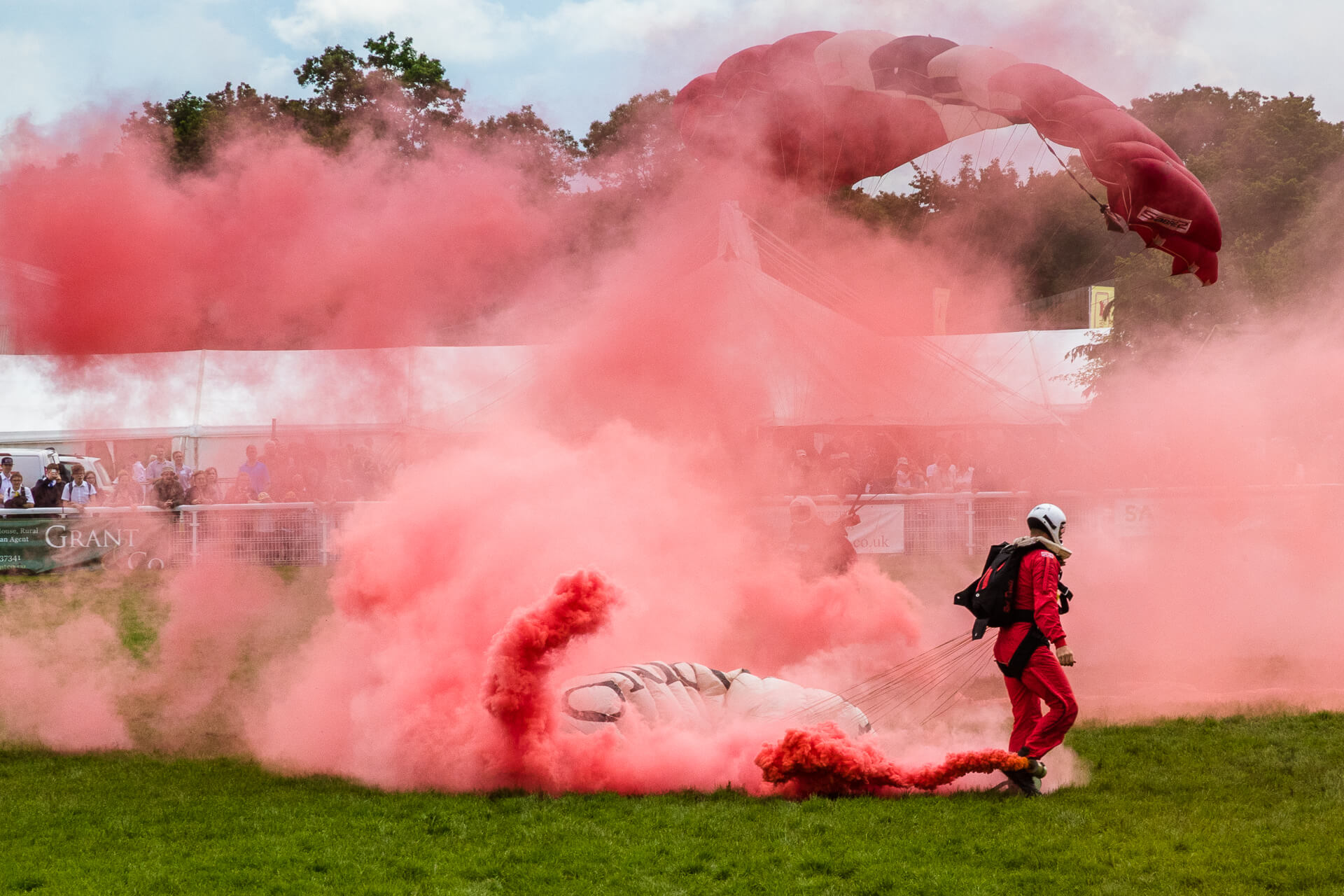 A colour image of 2 members of the Red Devils Parachute Team, the display team of The Parachute Regiment taken just after they landed at The 3 Counties Show, Malvern in 2017. The smoke canister attached to the right ankle of the nearest man still emits red smoke which billows around. The rear man can just be seen through the smoke as he tries to collapse his still inflated canopy.