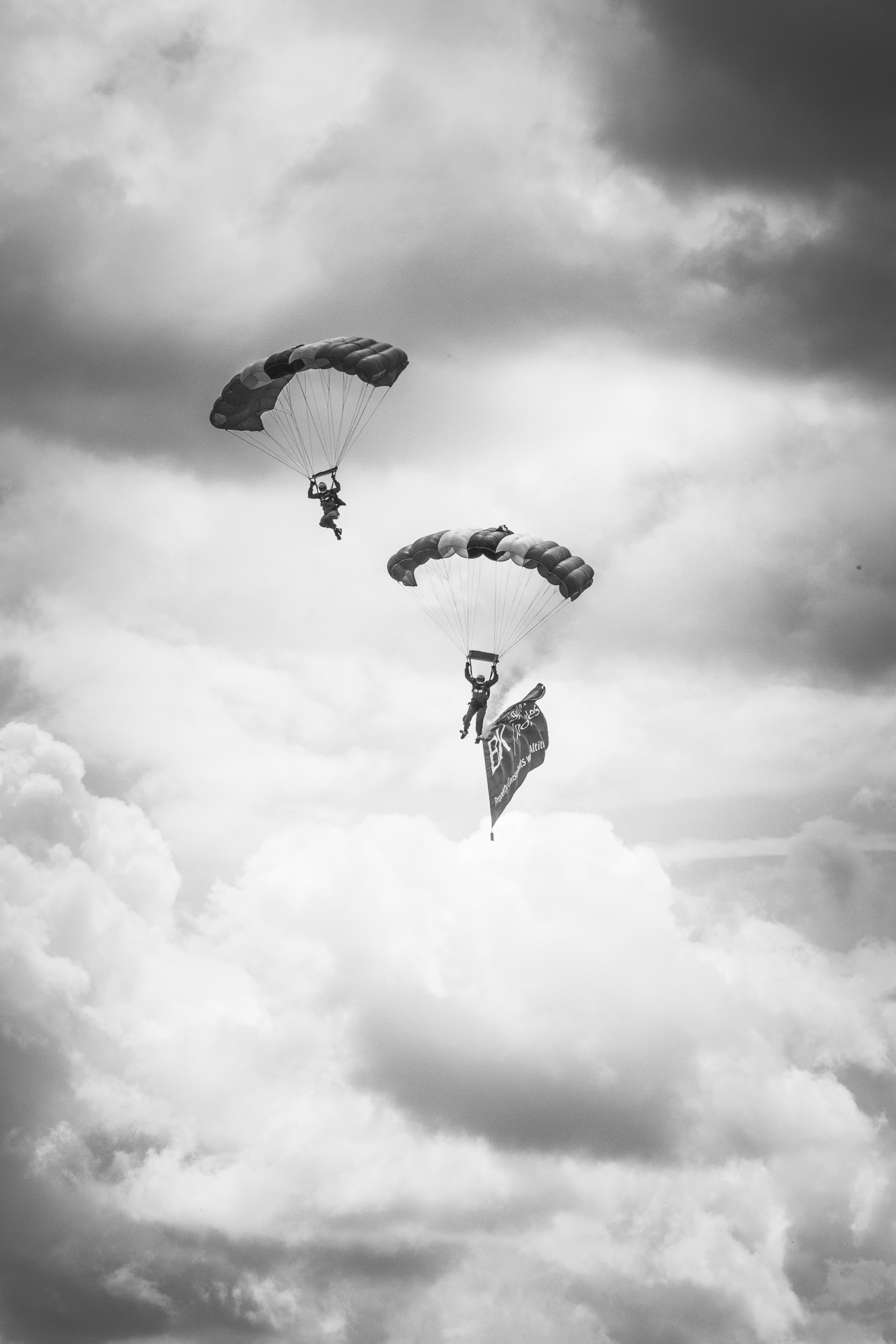 A black and white image of 2 members of the Red Devils Parachute Team, the display team of The Parachute Regiment. Taken just as they break from a stack on their final approach to land at The 3 Counties Show, Malvern in 2017. The lowest man carries a flag attached to his left leg which can be seen here trailing behind him.