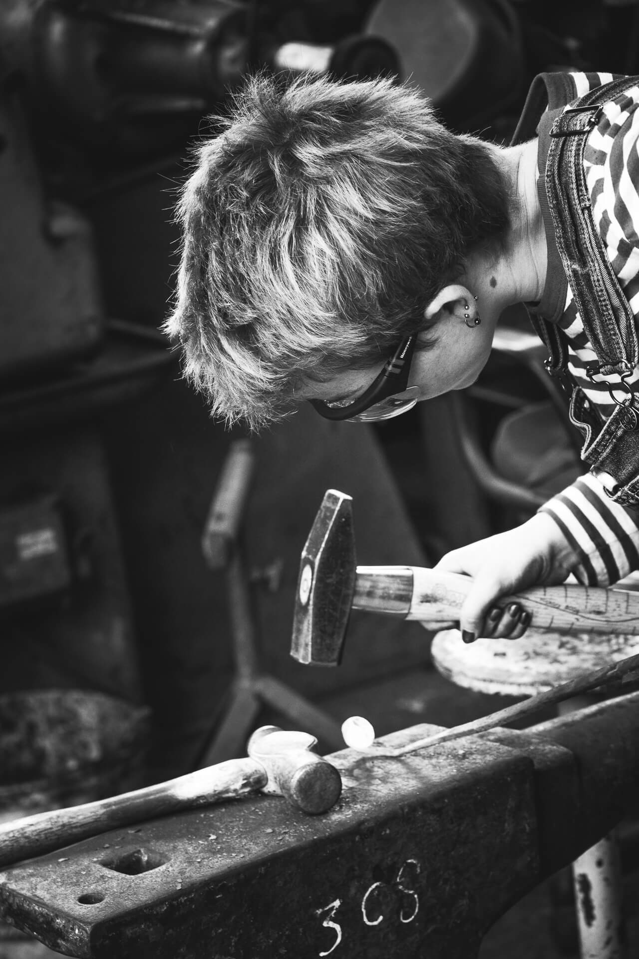 A close up black & white image of female blacksmith working red hot metal at a traditional anvil with a traditional blacksmiths hammer. She wears dungarees & protective glasses. She has very short spikes hair and strangely, painted nails!