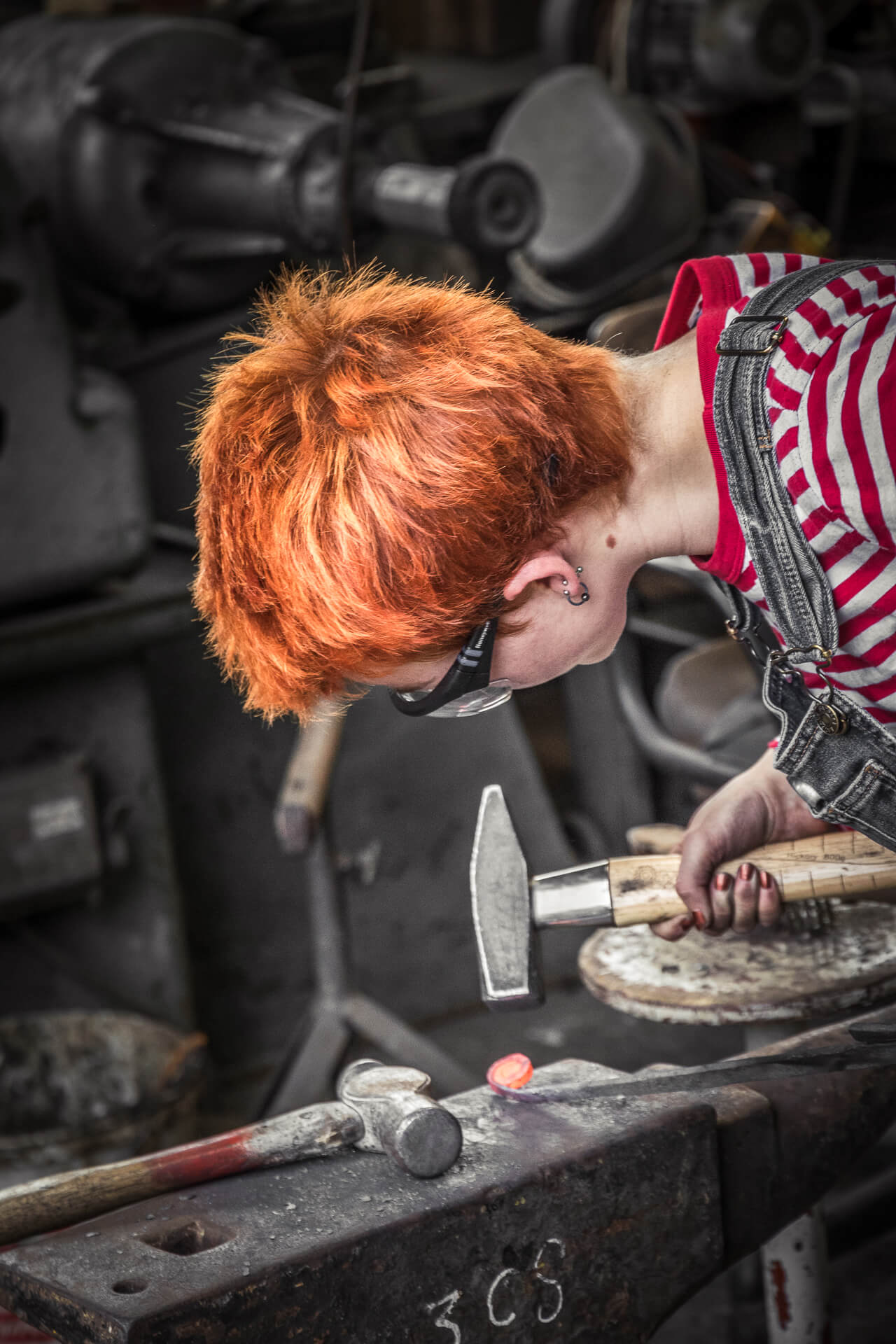 A close up colour image of female blacksmith working red hot metal at a traditional anvil with a traditional blacksmiths hammer. She wears dungarees & protective glasses. She has very short ginger spikey hair and strangely, painted nails!