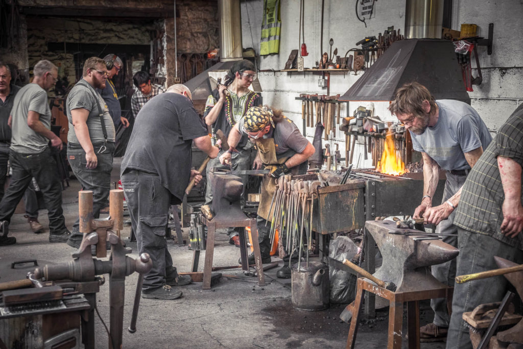 A colour wide angle image of the interior of a smithy. The image shows two blacksmiths working at their anvils, whilst the forge can be seen burning in the background. Other blacksmiths can be seen carrying out other tasks within the smithy.
