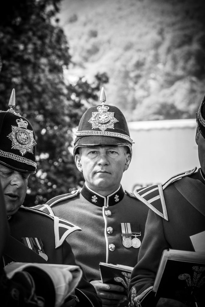 A black and white image (taken chest upwards) of an Army Musician taken as he waits to perform at the 3 Counties Show Ground in 2017. He appears to be part of a Welsh Regiment as both the ceremonial Pith Helmet centrepiece and the 'Collar Dogs' he wears have the Prince of Wales feather emblem and Ich Dien on them.