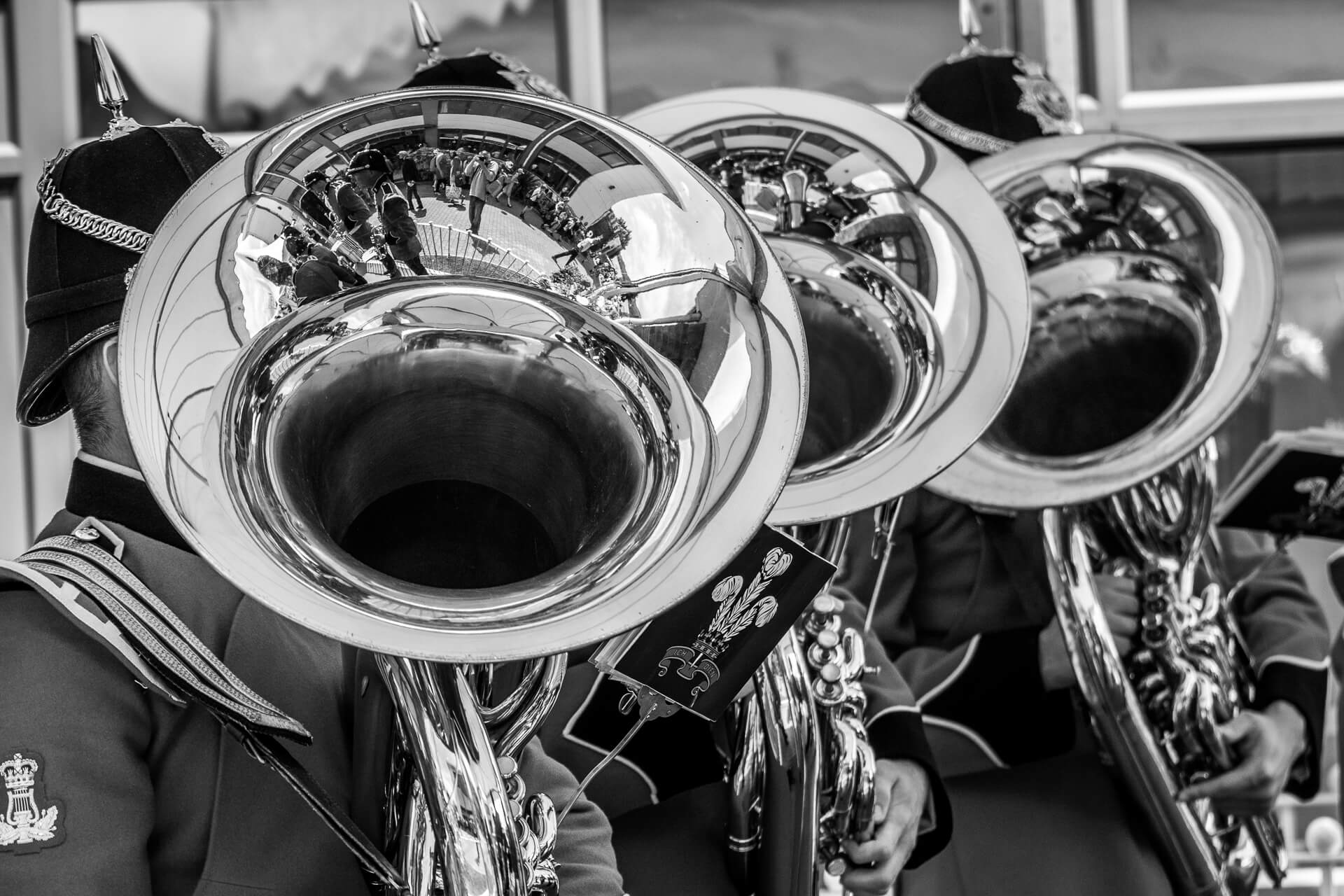 3 Army Bandsmen (Musicians) stand in the shade whilst waiting to play. Seen in black & white they are dressed in ceremonial dress and spiked ceremonial pith type helmets. They have their instruments slung across their chests mouthpieces at the ready.