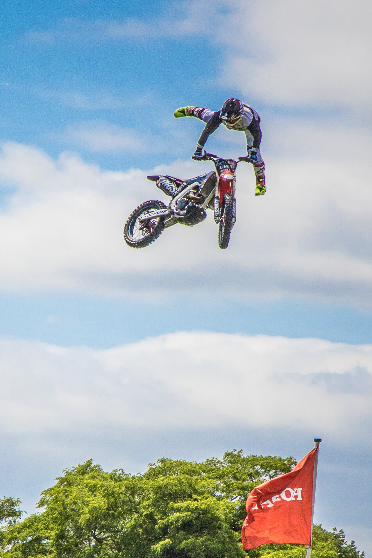 A motorbike stunt bike rider seen here, in full protective clothing and against a 'Simpson's Sky' background, getting some 'airtime' during a display at Bike For Life in 2018. He is seen here with only his hands on the handlebars, the rest of his body is off of the bike, his legs are above his head.