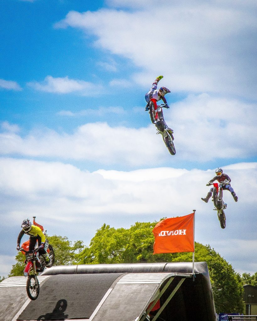 A trio of motorbike stunt bike riders are seen here, in full protective clothing and against a 'Simpson's Sky' background, in a trail formation as they all get 'airtime' during a display at Bike For Life in 2018.