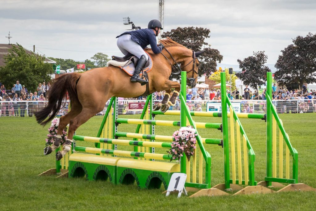 Seen from the rear right position just after taking off (and in a colour image) a horse and rider attempt to clear a set of 3 bars as they take part in the show jumping at the 3 Counties Show Ground.