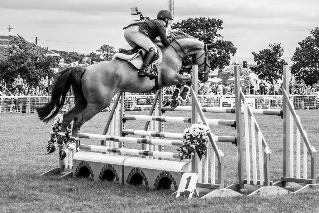 Seen just after taking off in a black & white image a horse and rider attempt to clear a set of bars as they take part in the show jumping at the 3 Counties Show Ground, Malvern.