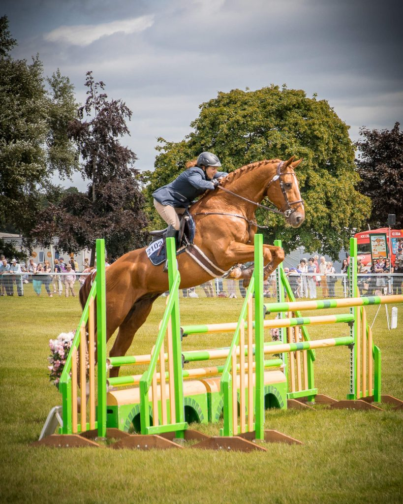Seen just as they take off (in a colour image) a horse and rider attempt to clear 3 sets of bars as they take part in the show jumping at the 3 Counties Show Ground. The horse is a very light brown in colour with a white flash down his nose, and the female rider wears a pony tail under her helmet.