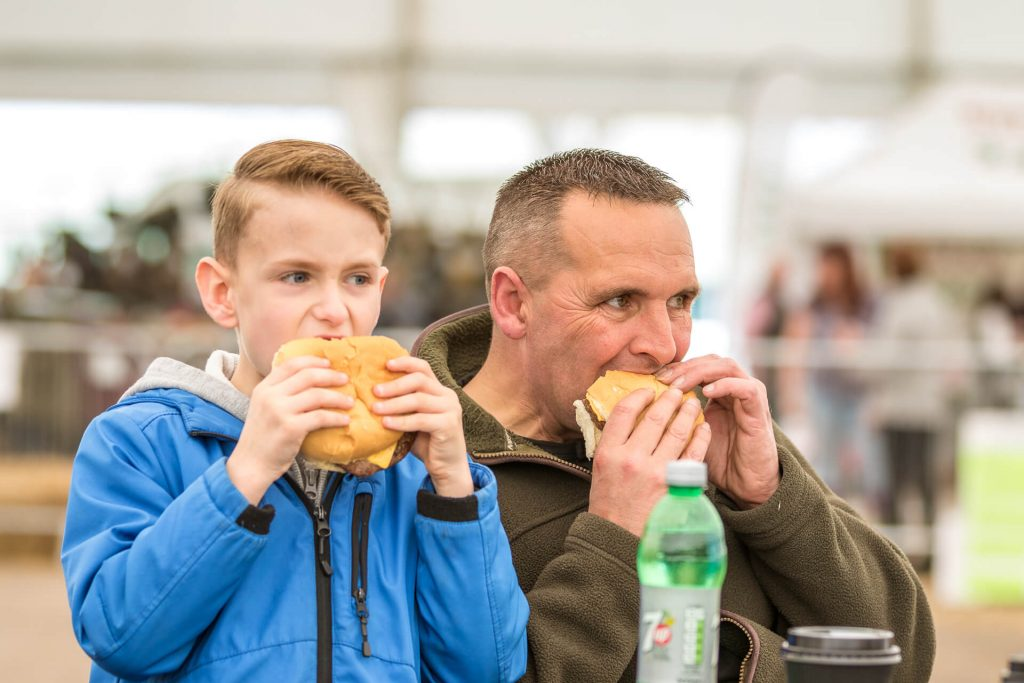 Seen in colour (this chest up image of) a Father & Son, sat side by side, both take a bite from their burgers at the same time as they watch something to slightly to their left. Taken at the 3 Counties Showground in Malvern.
