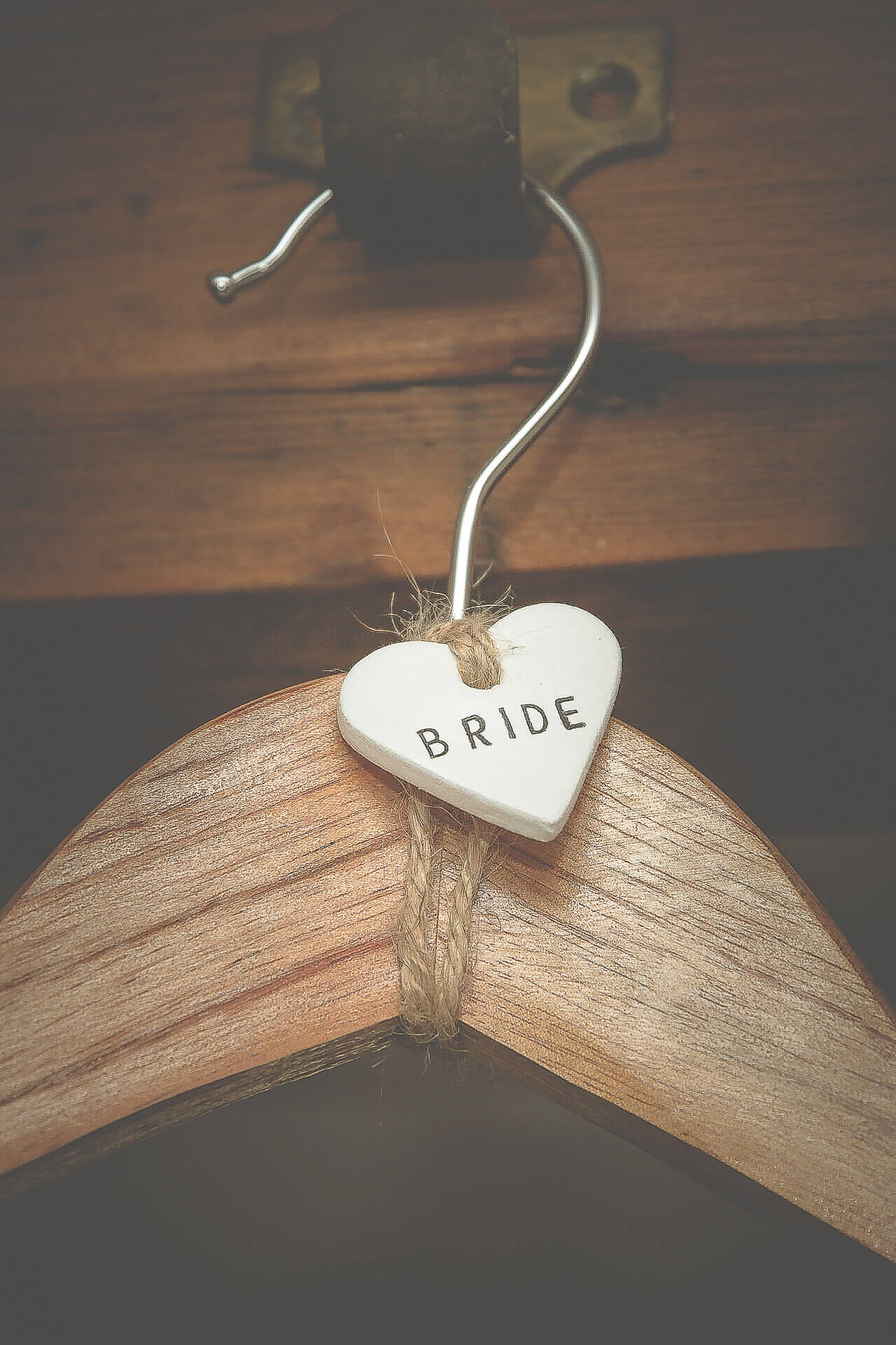 Close up image of the coat hanger holding the Bridal Dress. It has a small white ceramic heart attached to it on which is written Bride.