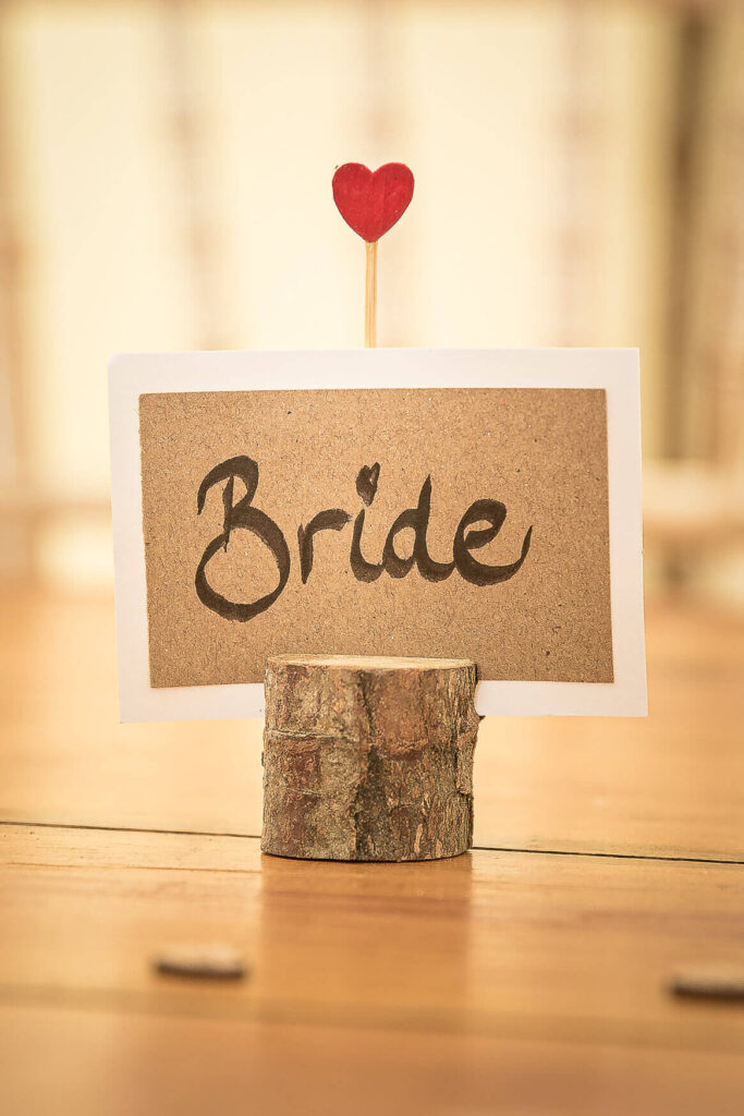 A small circular piece of wood with a narrow slot cut in the top with a piece of card inserted into the slot. The word Bride is written on the card. There is a small red coloured heart on a stick poking out of the top.