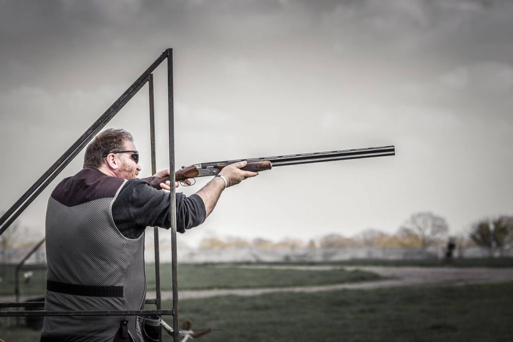 A 'shot' of a shooter! A semi desaturated image of a left handed competitor at the shoot taking place during the 3 Counties Show in Malvern. He waits for the clay to appear (whilst in a 'safety cage') with his 'over & under' shotgun ready in his shoulder, finger covering the trigger.