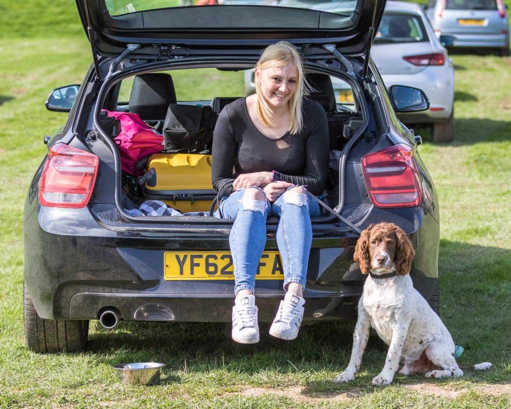 An image of a young lady and her dog. She sits in the back of her dark coloured estate car, legs dangling over the edge, whilst her liver & white coloured Spaniel sits on the floor, both look at the camera. She has shoulder length blonde hair, and she wears ripped skinny jeans, white trainers, and a very tight black top.