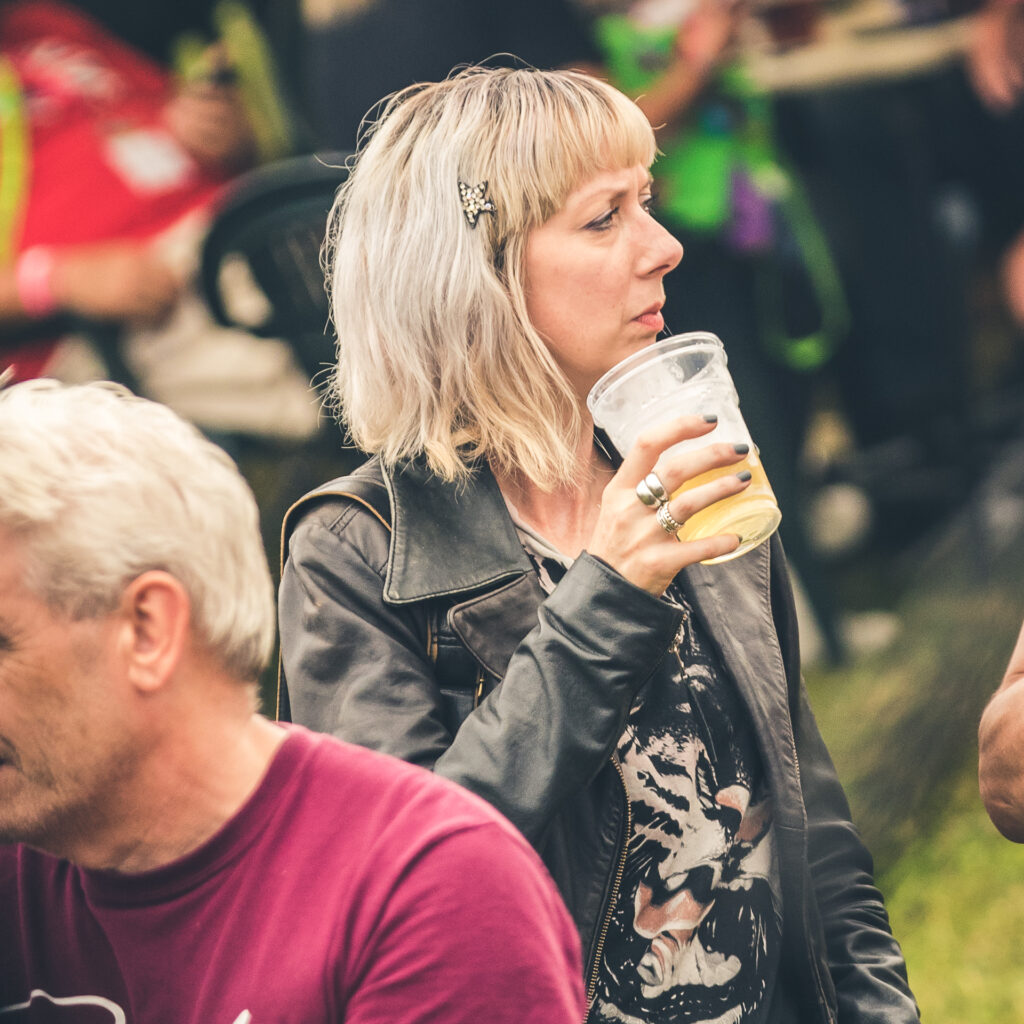 A waist up colour image of a blonde haired 'Lou' at The Drunken Monkey Rock Festival. Lou is seen here wearing a black T-shirt and black leather jacket as she drinks from a plastic glass.
