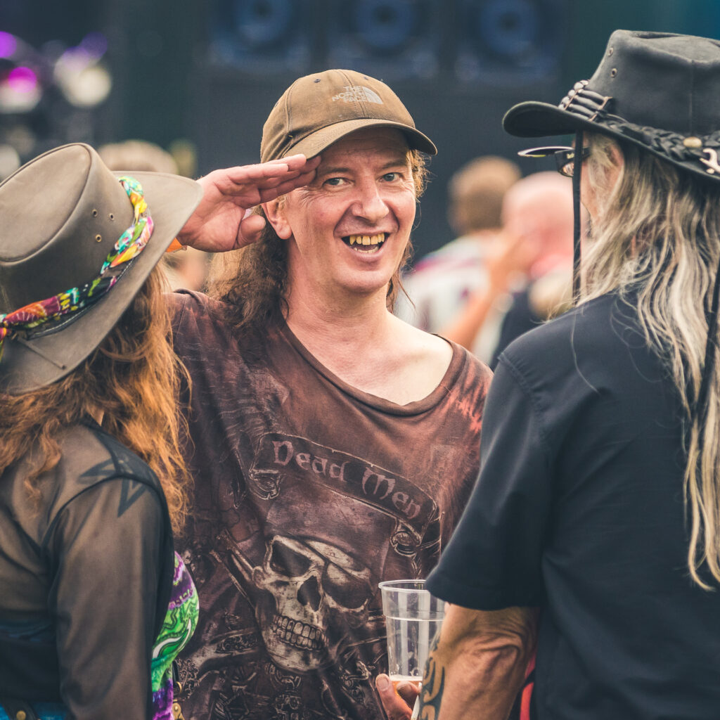 """Steve, the bass player with The Wizards of Oz, smiles and salutes the camera (with a Royal Navy style salute) as he notices his photograph being taken. He is stood facing the camera talking with 2 friends (who are backs to the camera) at the Drunken Monkey Rock Festival 2019. Steve wears a brown """"Dead Men Tell No Tales"""" T-Shirt by The Mountain, and a light brown North Face baseball cap."""