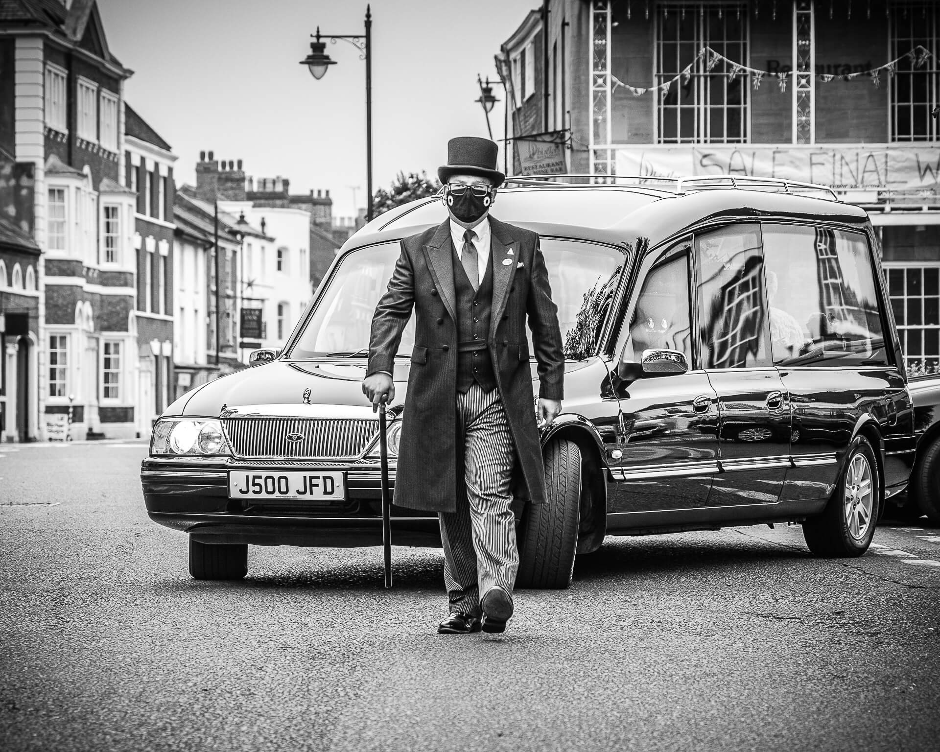 A Funeral Director wearing a COVID mask pages in front of a coffin ladened Hearse