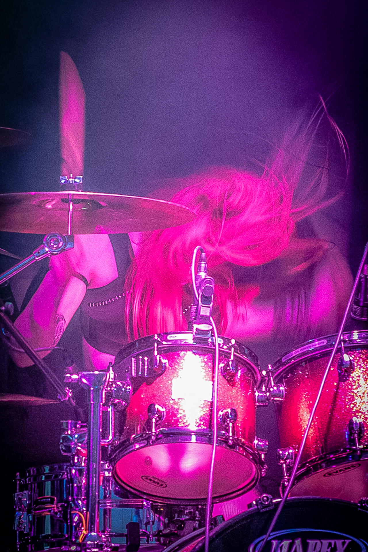 Alice, a female drummer, is seen here behind her drum kit with a now defunct band Aramantus at Mappfest, Malvern. In this deliberately blurred image Alice, with her shock of pink hair, is playing with full on passion.