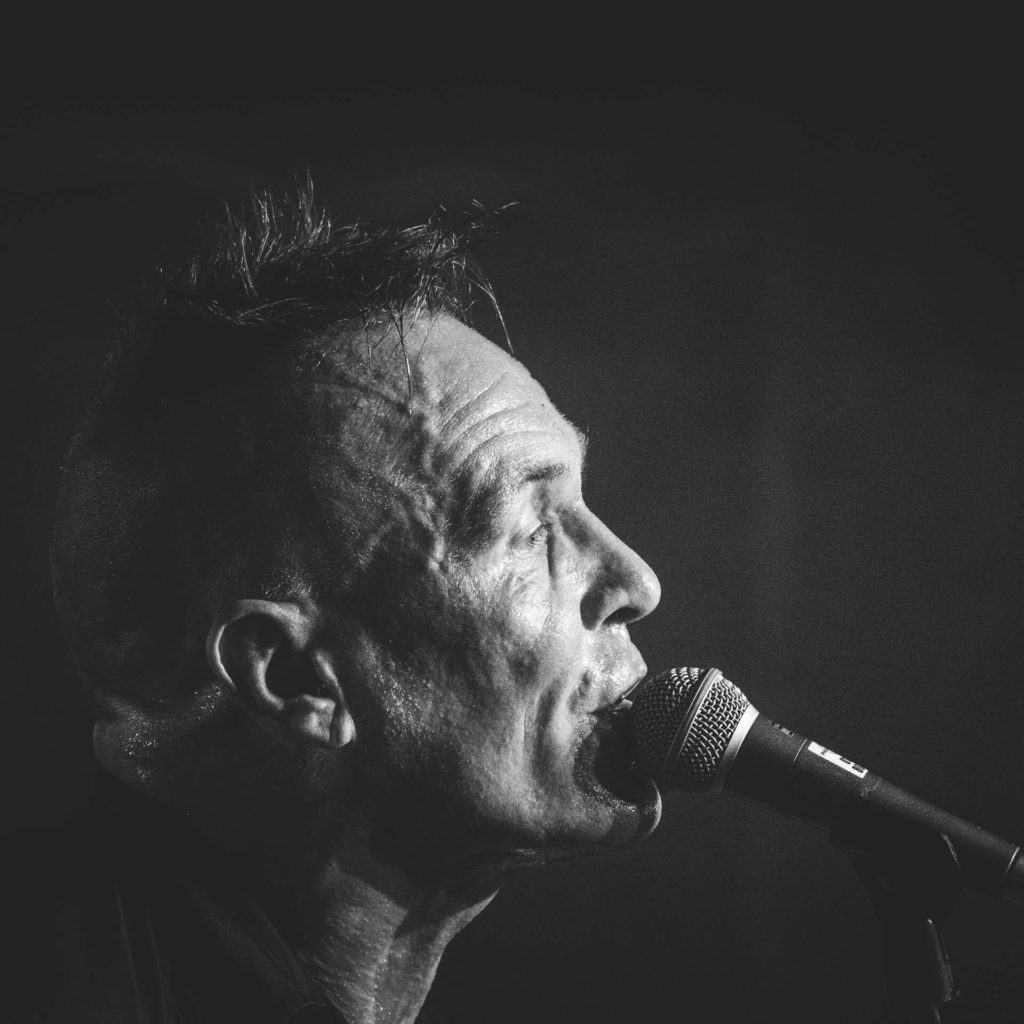 A B&W headshot of Mr John Robb lead singer with The Membranes at the microphone on stage at Lakefest 2019