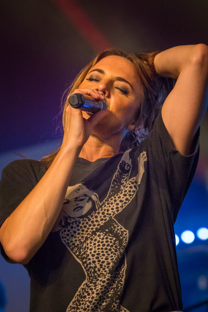 A colour image of Mel C (aka Sporty Spice) microphone to her mouth, and her left hand held behind her head performing at Lakefest 2019.