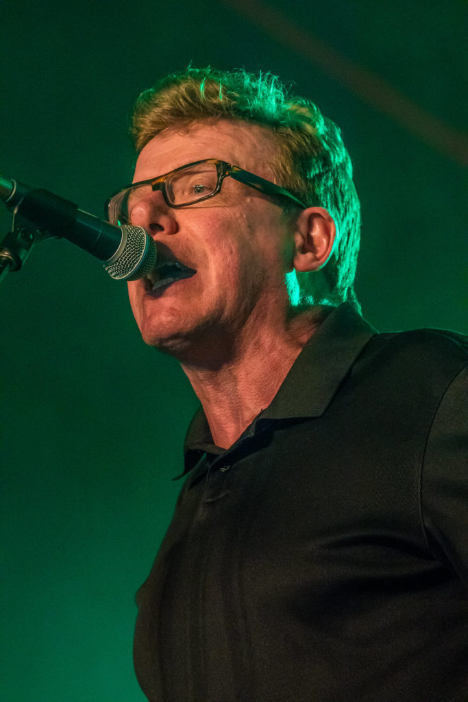 A close up 3/4 head & shoulders image of Charlie Reid of The Proclaimers singing whilst performing at Lakefest 2019.