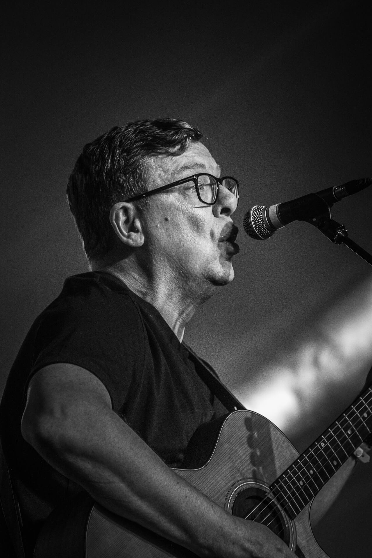 A close up B&W head & shoulders image of Craig of The Proclaimers playing guitar & singing whilst on stage at Lakefest 2019.