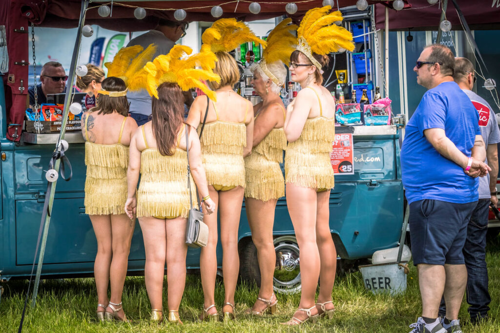 A colour image of 5 members of the Jewels Burlesque and Cabaret Troupe at the Dubs of Anarchy Festival 2019. They stand in a line waiting for coffee to be served at a converted VW Transporter.