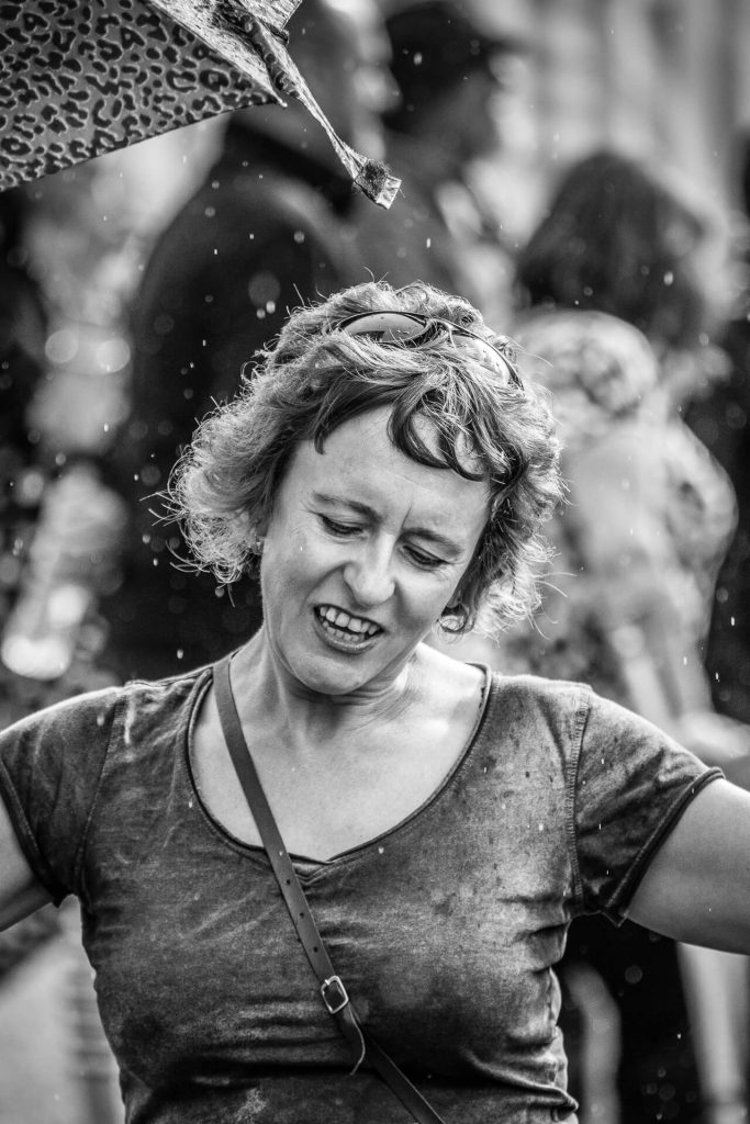 A black & white chest up image of Vicky at the Drunken Monkey Rock Festival 2019. She is seen here with a smile on her face as she holds her umbrella and dances in the rain.