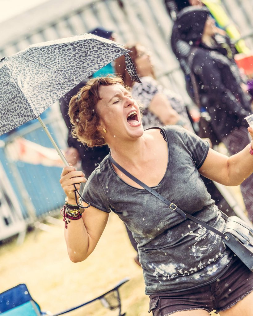 A waist up colour image of my good friend Vicky at the Drunken Monkey Rock Festival 2019. She is seen here as she sings and dances in the rain. She holds her leopard skin design umbrella in her right hand, and in her left is a pint, no surprise there!