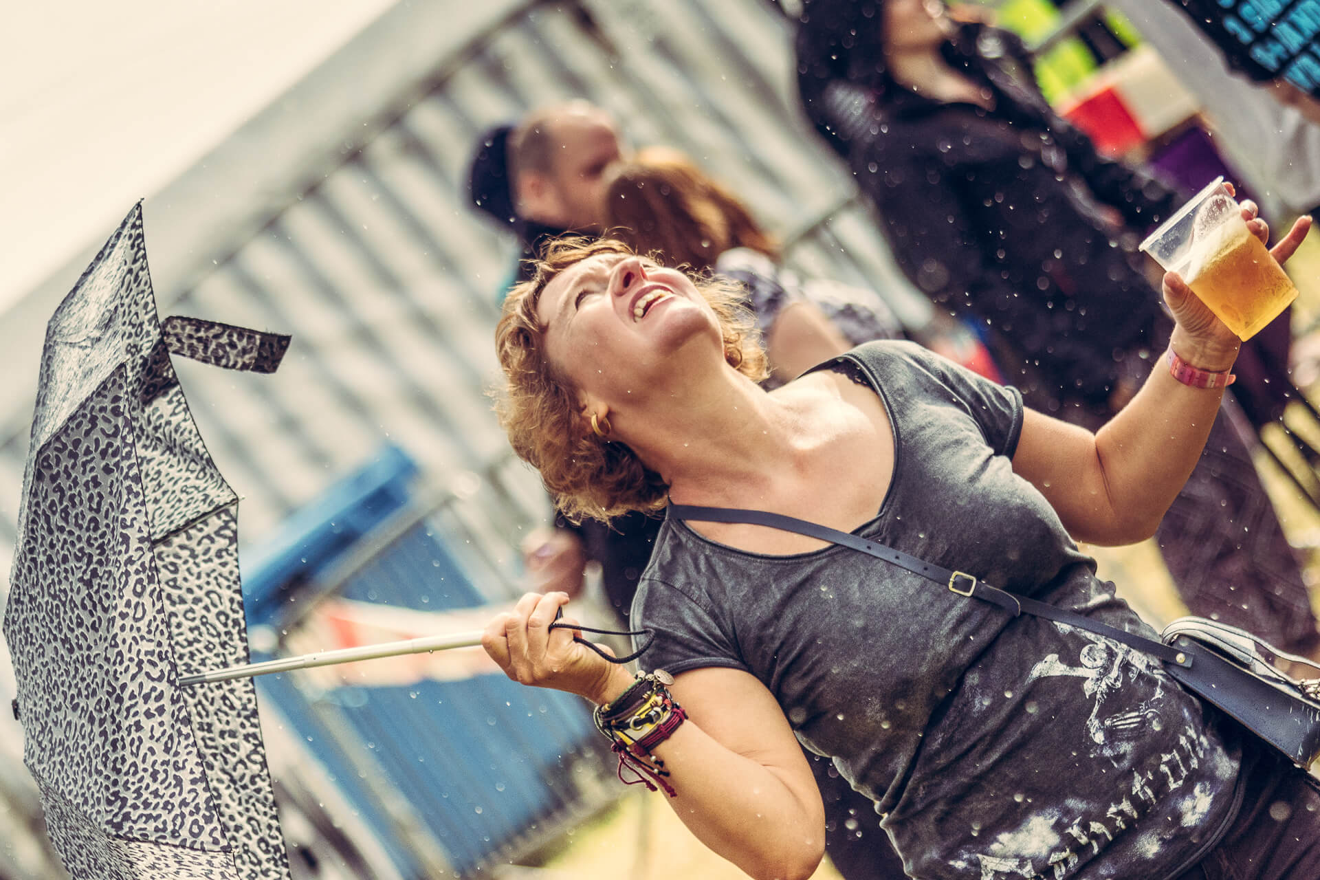 A waist up colour image of Vicky at the Drunken Monkey Rock Festival 2019. She is seen here as she dances in the rain. She holds her leopard skin design umbrella in her right hand, and out to her side as looks to the sky at the falling rain.