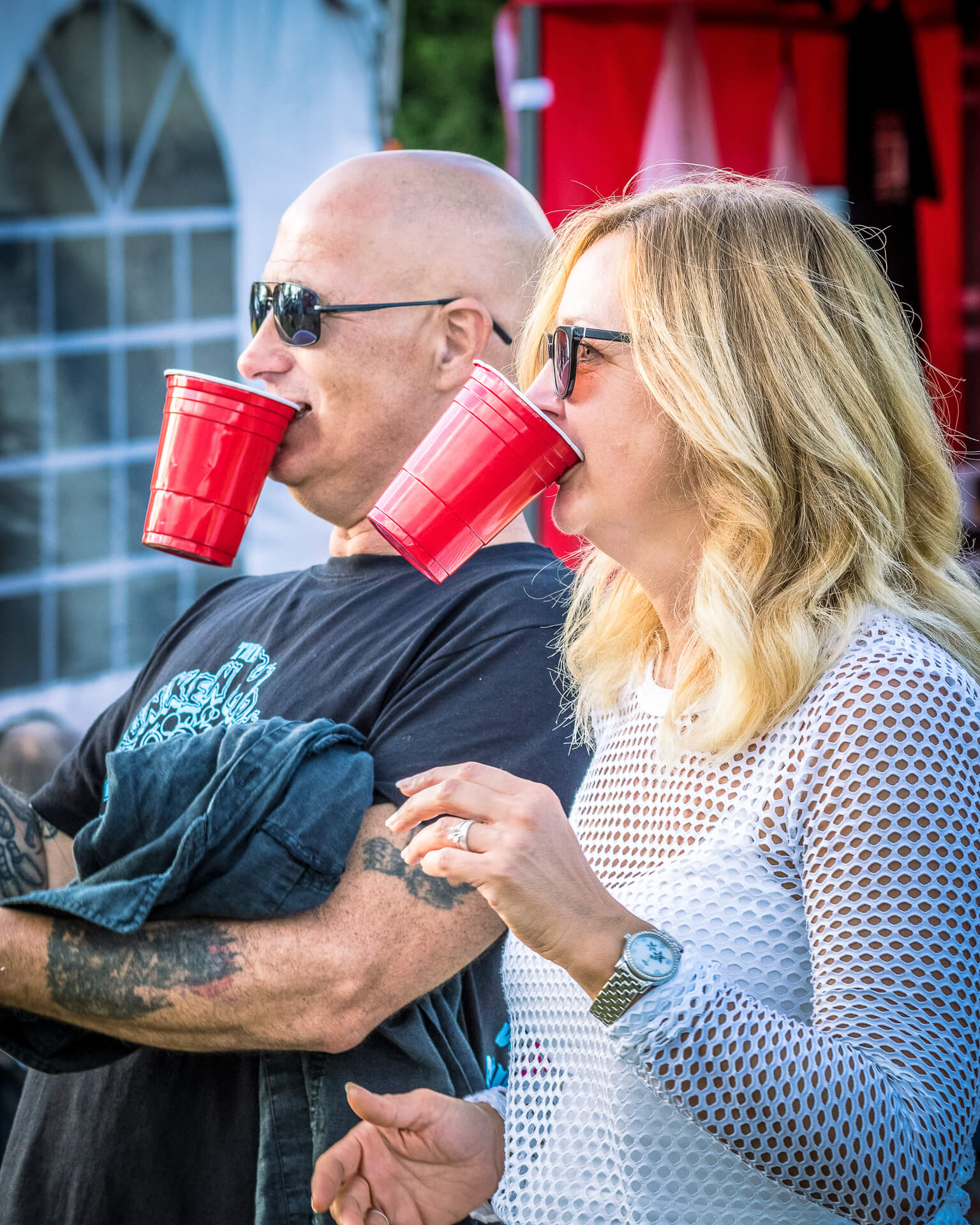 A waist up shot of a couple as they stand together at The Drunken Monkey Rock Festival applauding. To save putting their red plastic glasses down on the ground they both hold them in between their teeth!