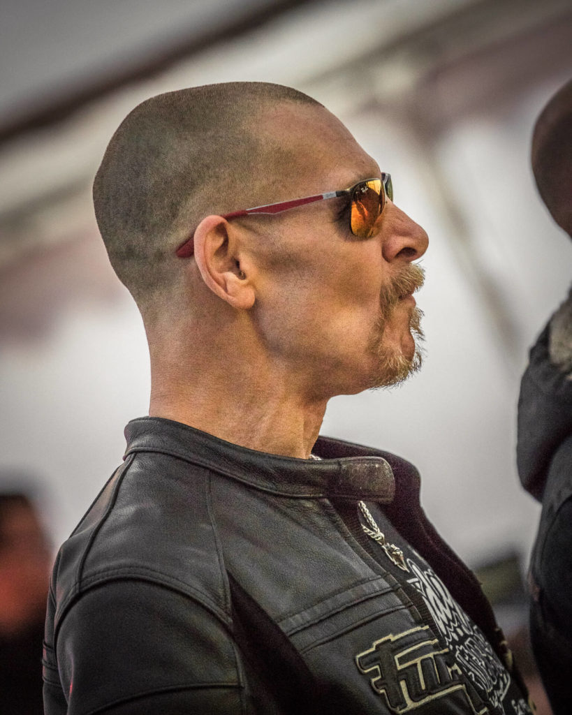 Dave, seen here in a colour chest up image, watches as a band perform on stage. His shaved head, wire goatee, and reflective sunglasses give him (incorrectly) a rather menacing appearance!