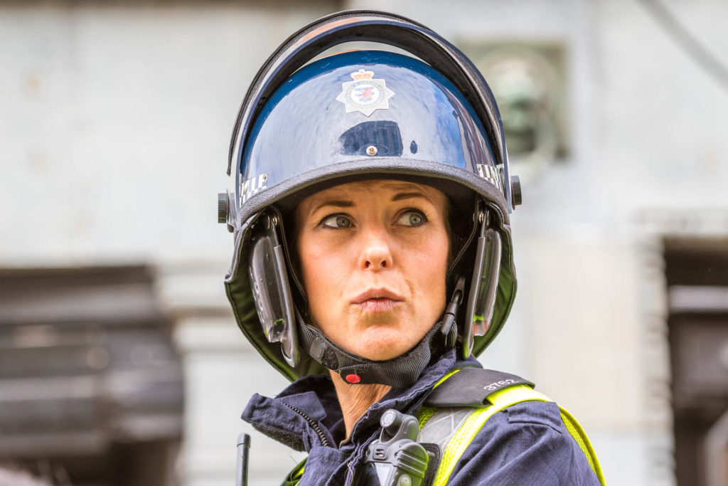 A close up head shot of PC 3762 of the Avon & Somerset Police atop her Police Horse at the BNP Marches in Worcester in 2019. She is seen here wearing her protective helmet with the vizor up as she looks up and to her left during the build up to the march taking place.