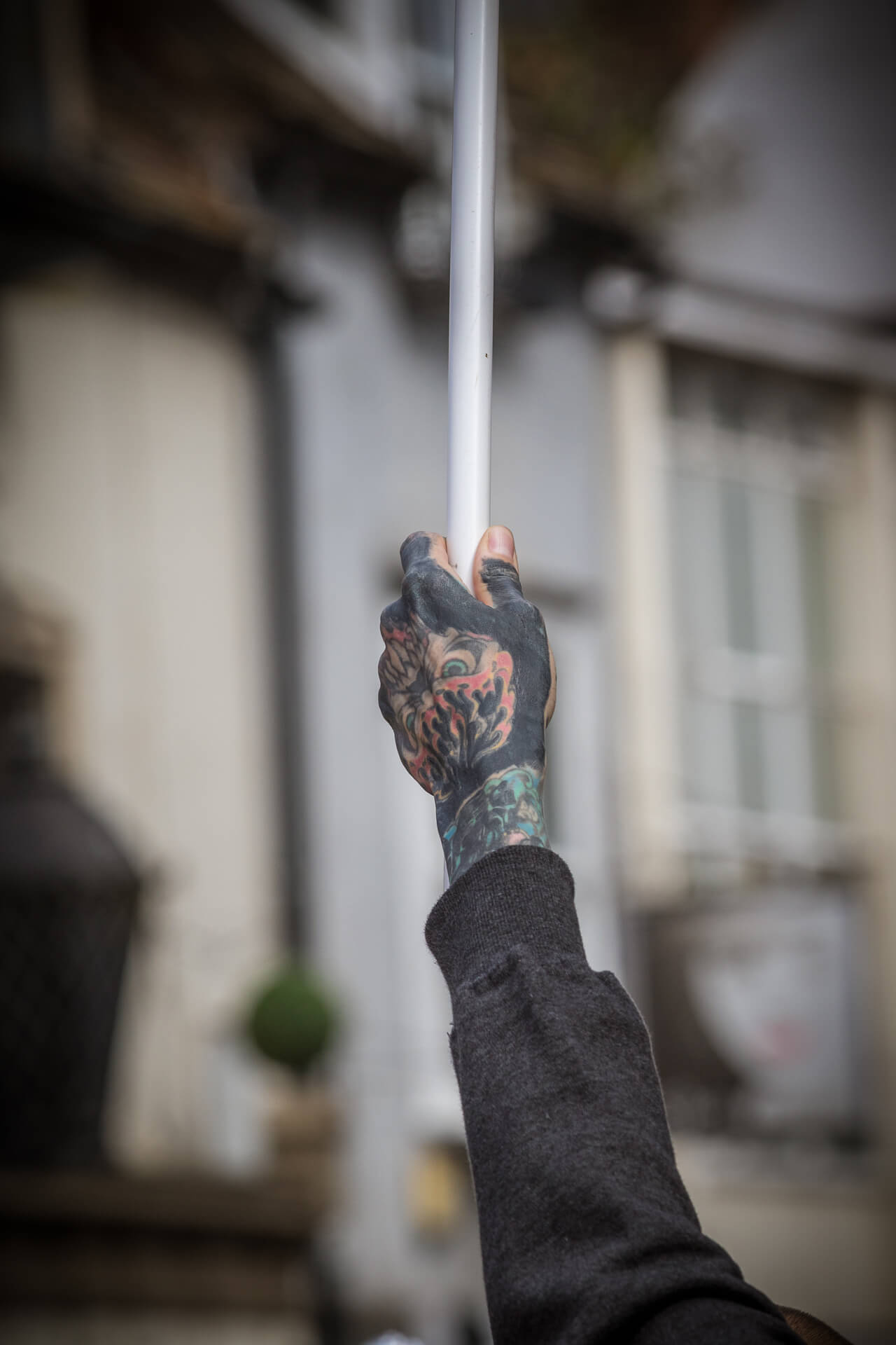A colour image, taken from a distance, of the heavily tattooed hand of one of the individuals participating in the BNP Marches in Worcester in 2019. He holds aloft a flag attached to a thin white pole.