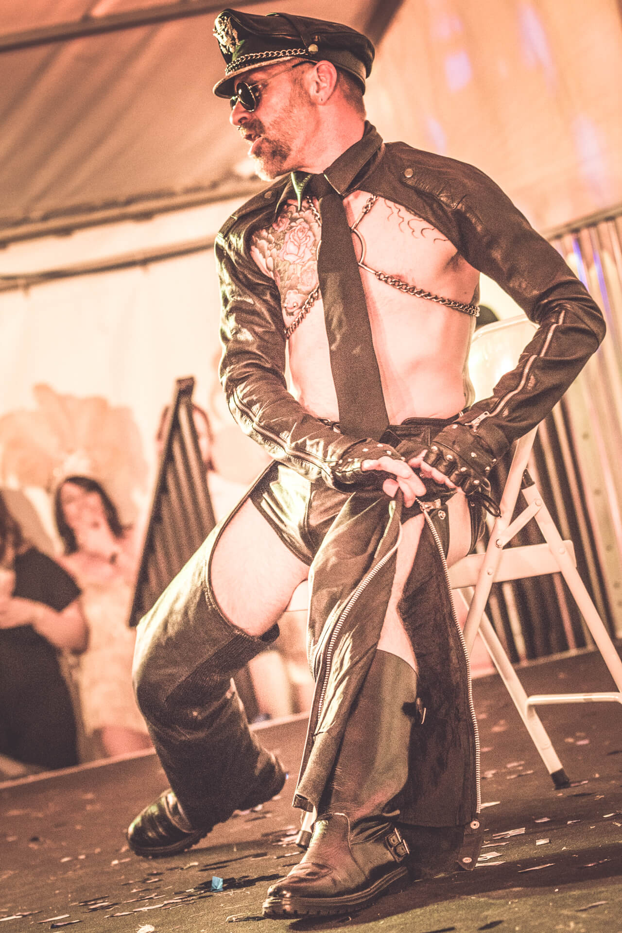 An onstage shot of a male burlesque performer taken at Dubs of Anarchy in 2019. He is seen sat on a chair as he unzips and removes his leather chaps. He (still) wears a leather cap with a chain band, a chain chest harness, tight leather shorts, a leather shrug with zips, a neck tie, fingerless gloves, biker boots, and black aviator sunglasses.
