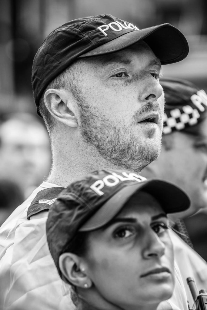 A black & white image of two Police Officers as they await the marchers at the 2018 BNP Marches in Worcester. The bearded male officer stands a complete head taller than his shorter female companion. Both wear baseball caps with POLICE written on them. He appears to be interested in something just in front of him on his right hand side, whilst she looks to her right towards the camera.