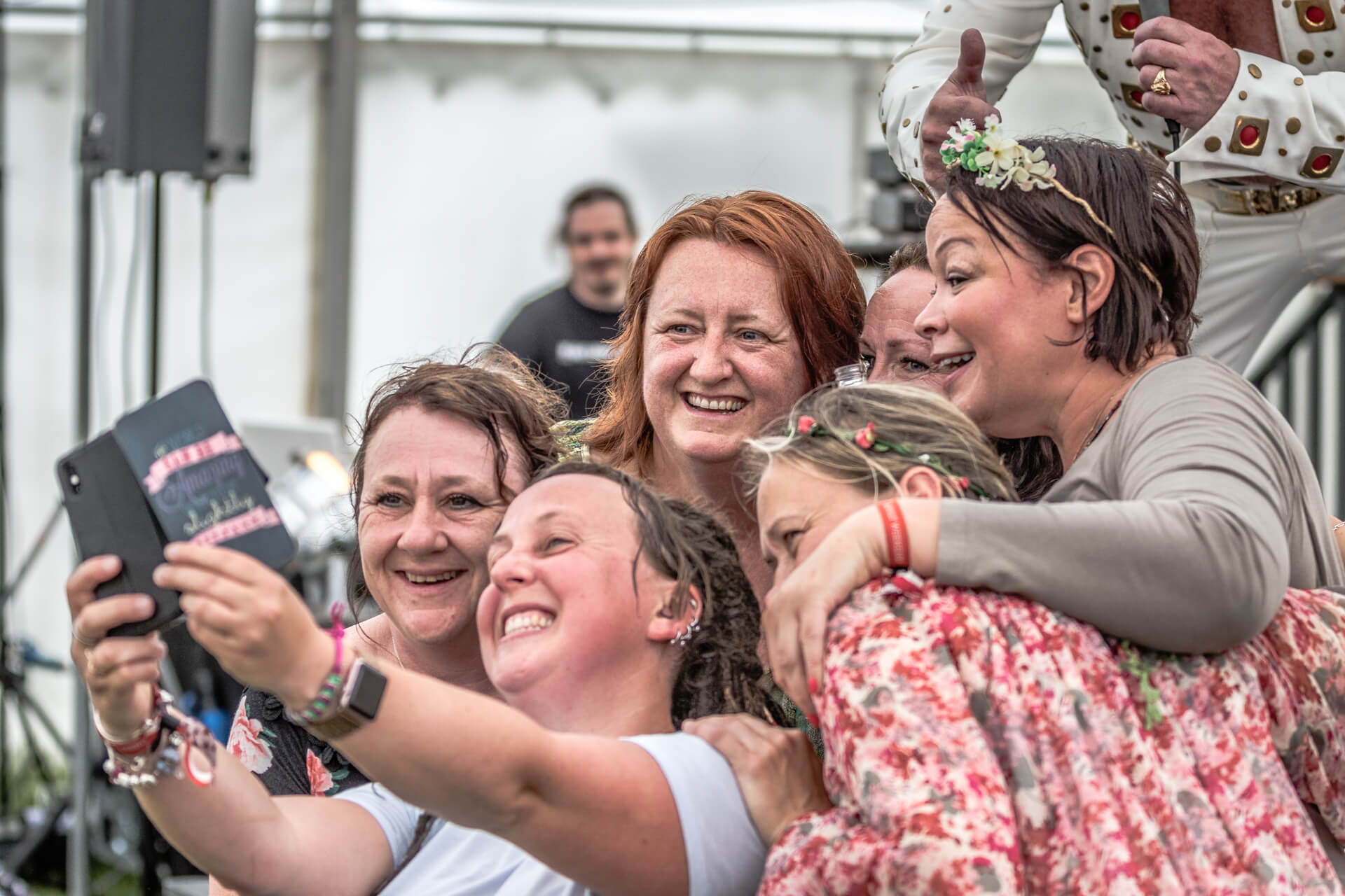 A colour image of a group of 6 female friends gather around and grin manically as they take a 'selfie' with a phone camera. They are standing at the edge of the front of the stage where an Elvis impersonator was performing. He can just be seen knelt down at the back of the group giving a 'thumbs up'.