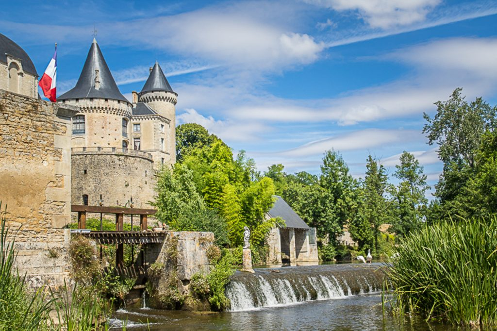 A view from the river side of the Chateau at Verteuil-sur-Charante, France. Set against a beautiful blue sky with cumulus clouds the magnificent buildings over look the river. The French Tricolour flies beside the weir.