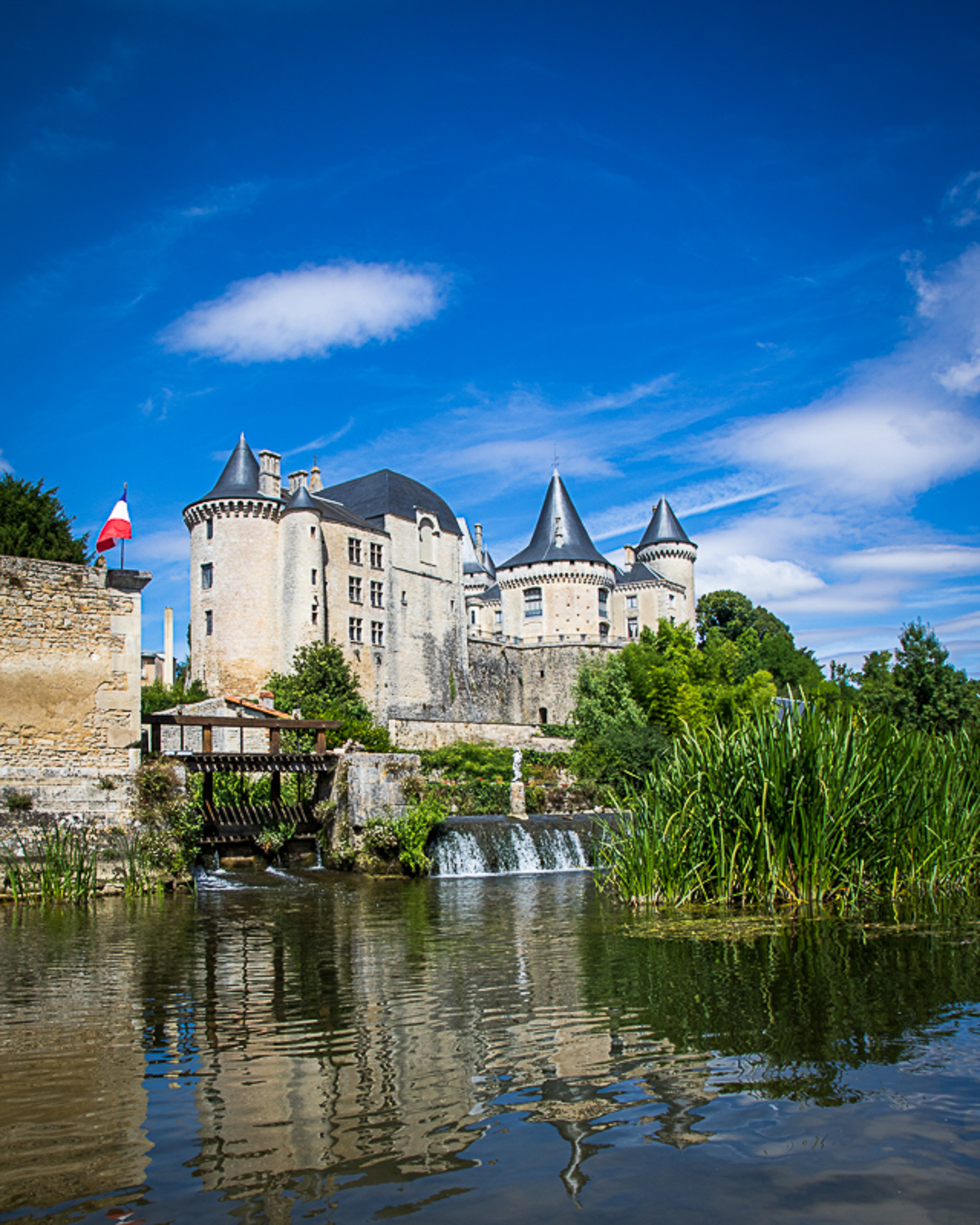 Taken from within the river a view of the magnificent buildings with their dark grey slate roofs of the Chateau at Verteuil-sur-Charante, France. Set against a beautiful blue sky, spattered with stratocumulus clouds, they overlook the Charente River. The French Tricolour flies beside the weir.