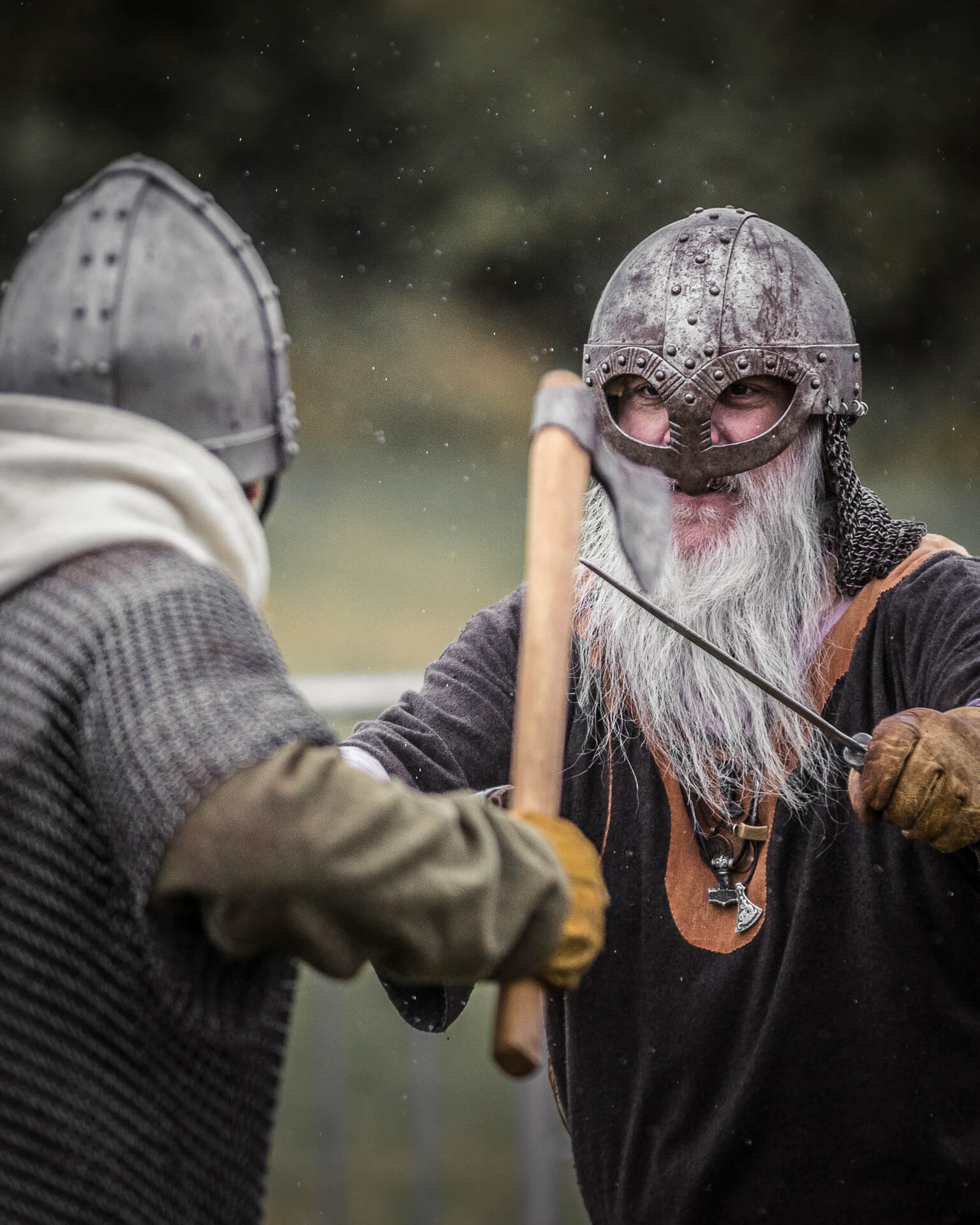 A colour image of two re-enactors staging a fight between (probably) combatants in the Saxon / Viking eras. One, carrying a fighting axe, wears a pointed steel helmet and a chain mail gillet whilst the other who carries a short sword wears a rounded helmet with cheek protectors. Both wear gauntlet type gloves.