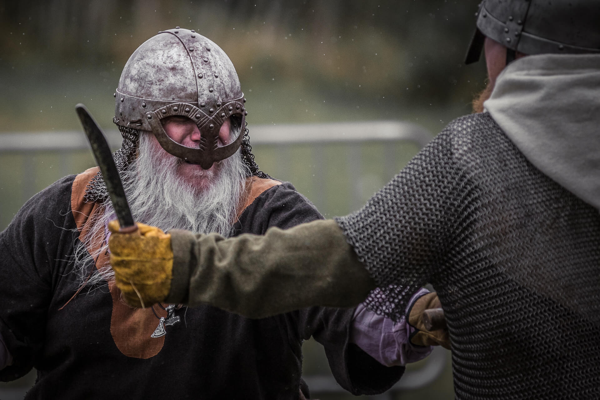 A colour image of two re-enactors staging a fight between combatants in the Saxon / Viking eras. One wears a rounded helmet with cheek protectors, and the other wears a pointed steel helmet and a chain mail gillet, whilst he carries a short stabbing sword.