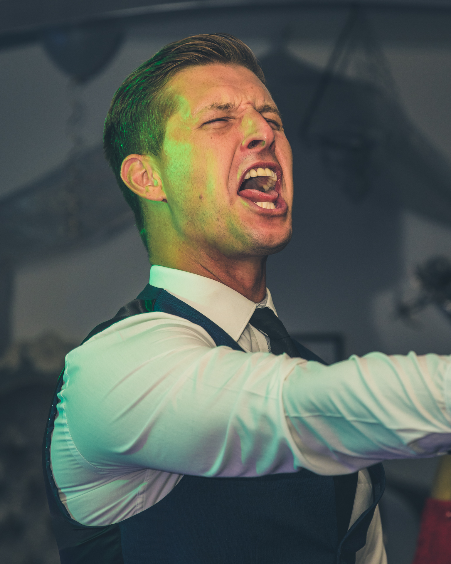 A chest up colour image of Mr X seen here on the dance floor at a company birthday party. He has his right arm extended and appears to be 'singing' (mouth wide open) whilst dancing. He wears a white shirt and a dark coloured waistcoat, and he has his hair swept backwards.