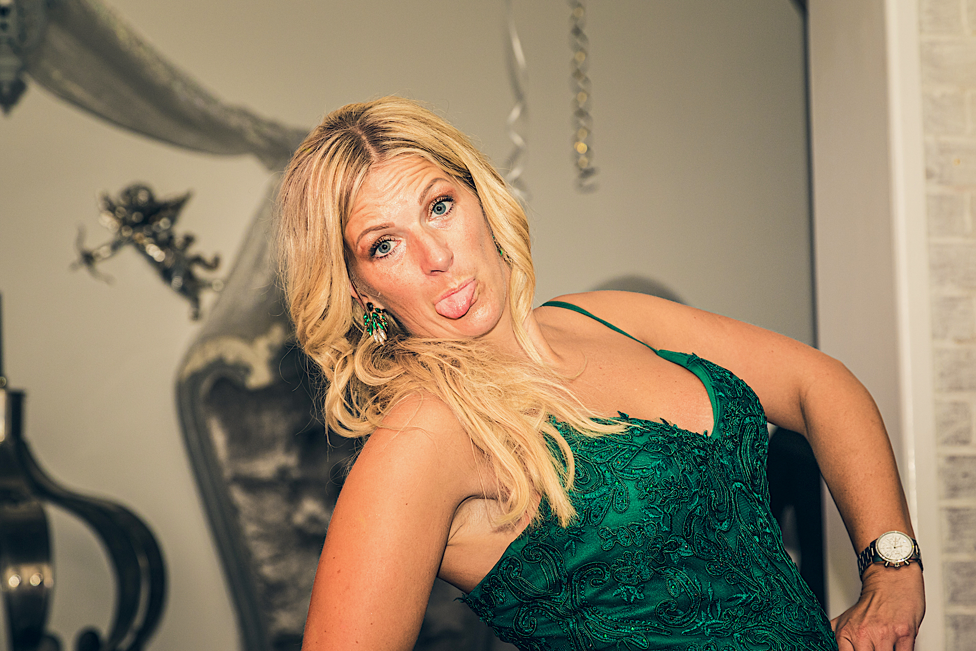 A colour waist up image of Kelly, seen here posing for the camera, whilst on the dance floor at a company birthday party. She wears a dark green cocktail style dress, and matching earrings. She has her arms on her hips as she leans slightly backwards and she sticks her tongue out at the camera!