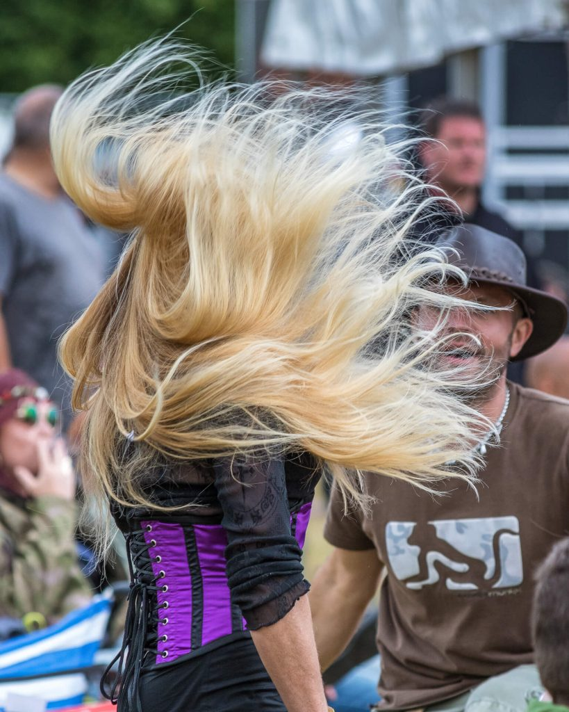 A colour image of member of the audience at the Drunken Monkey Rock Festival in 2018. As she dances her long blonde hair obscures her head completely allowing you to see only her waist and chest. Her hair looks like a blonde explosion! She wears a purple corset and a black shirt as she dances; a male audience member wearing a leather brim style hat, and who is partially obscured by her hair explosion, looks on!