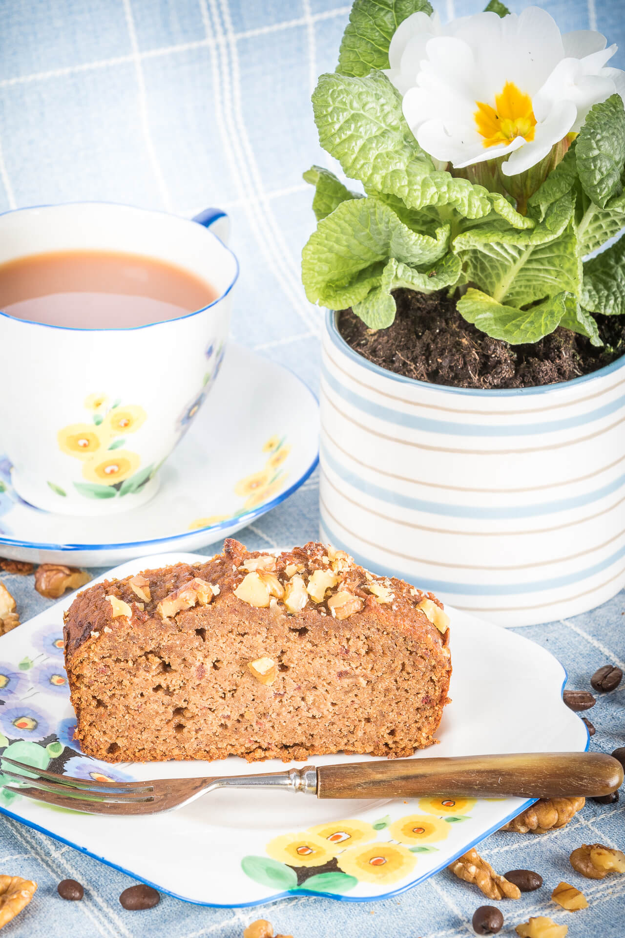 A Slice of Gluten Free Healthy Coffee & Walnut Cake On A Plate With A Cup Of Tea & A Potted Flower