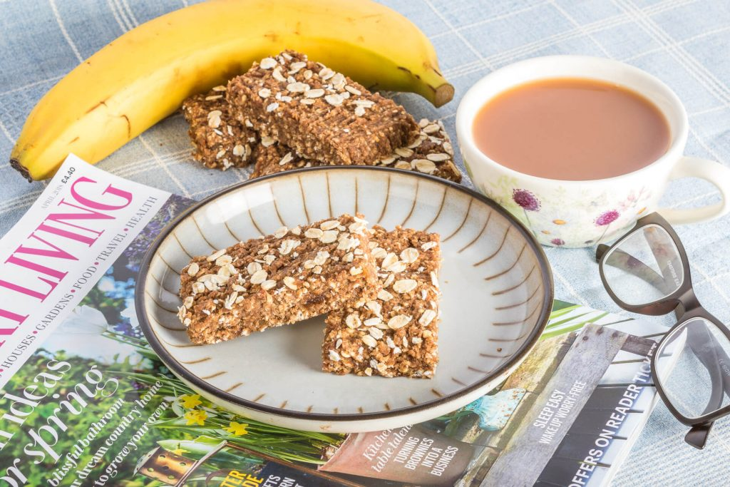 Two Gluten Free Nutritional Healthy Raisin & Oat Bars On A Plate With A Banana, A Cup Of Tea, A Pair Of Spectacles, And A Copy Of Country Life