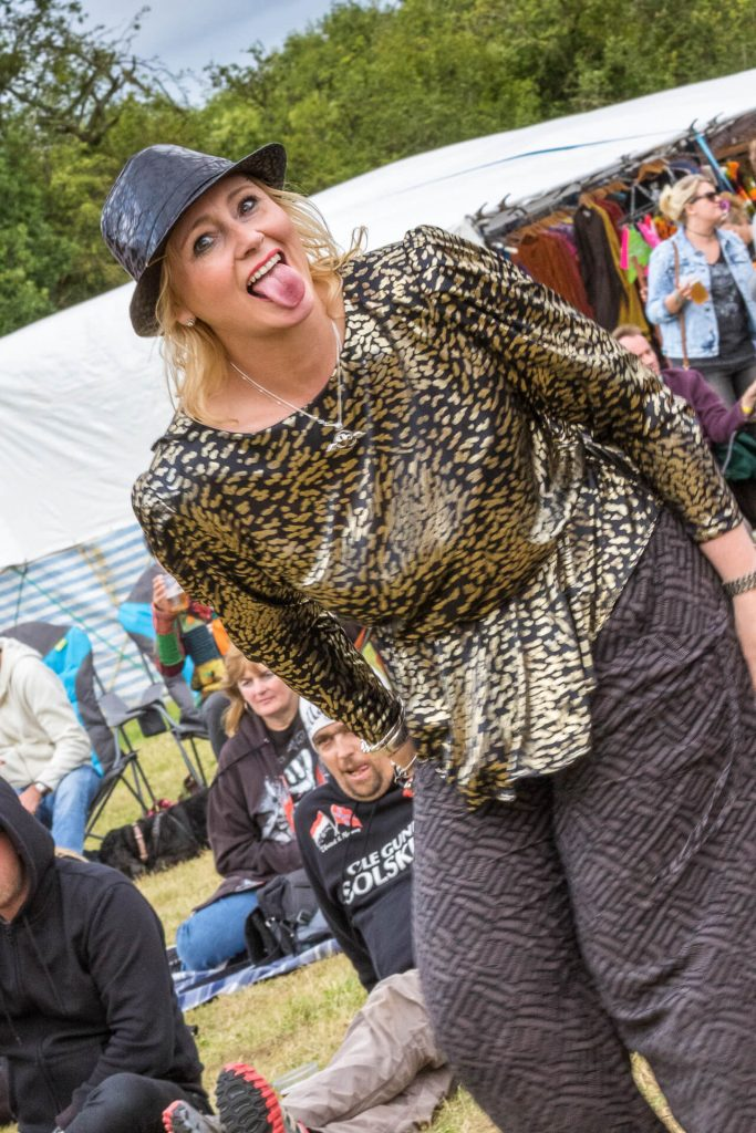 A 3/4 length image of a female festival goer at The Drunken Monkey Rock Festival. Seen in colour she has shoulder length blonde hair, she wears a black & gold top, with black baggy trousers, and she also wears a leather brimmed hat. She looks directly into the camera and she has her tongue sticking out.