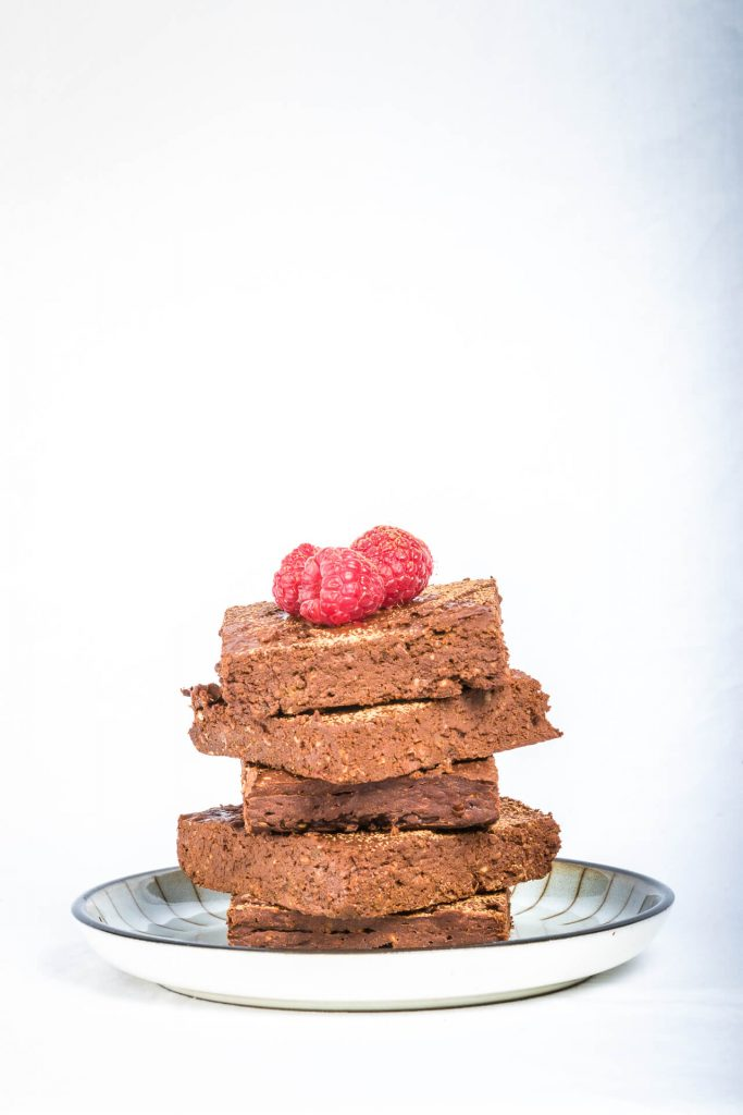 A Stack Of Five Gluten Free Chocolate Brownies with Fresh Raspberries As A Topping