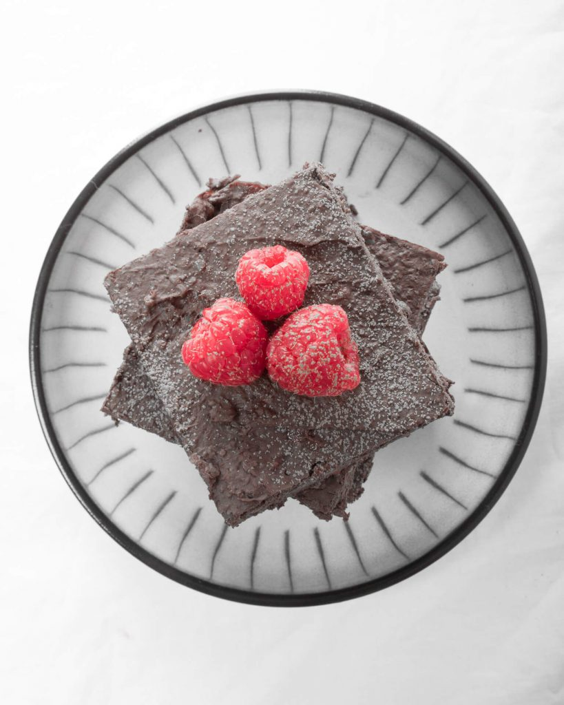 A Stack of Gluten Free Chocolate Brownies Topped With Three Fresh Raspberries In Black & White (Viewed From Above)